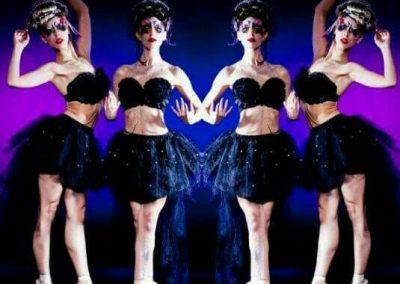 four ballerinas in black swan outfits en pointe
