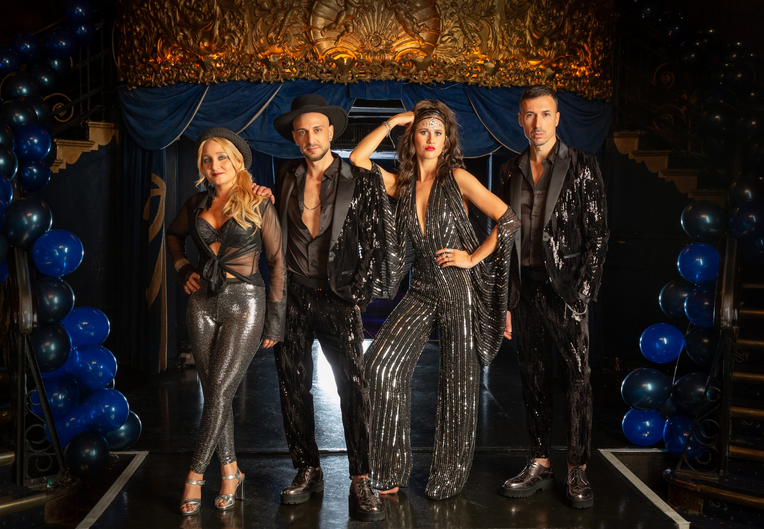 Four piece band, two male and two female in dark sequin show costumes standing on the stage of cafe de paris close up