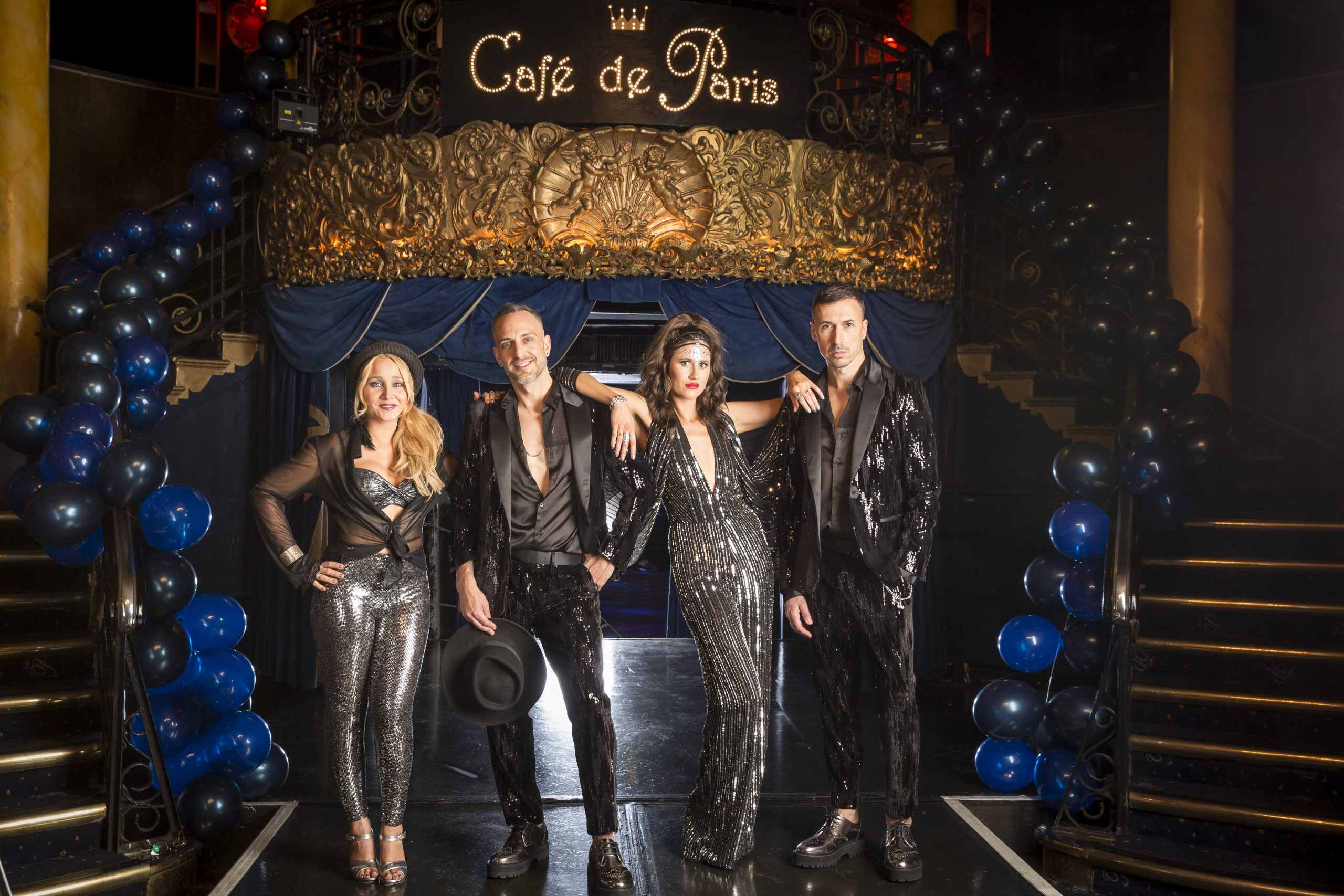 Four piece band, two male and two female in dark sequin show costumes standing on the stage of cafe de paris