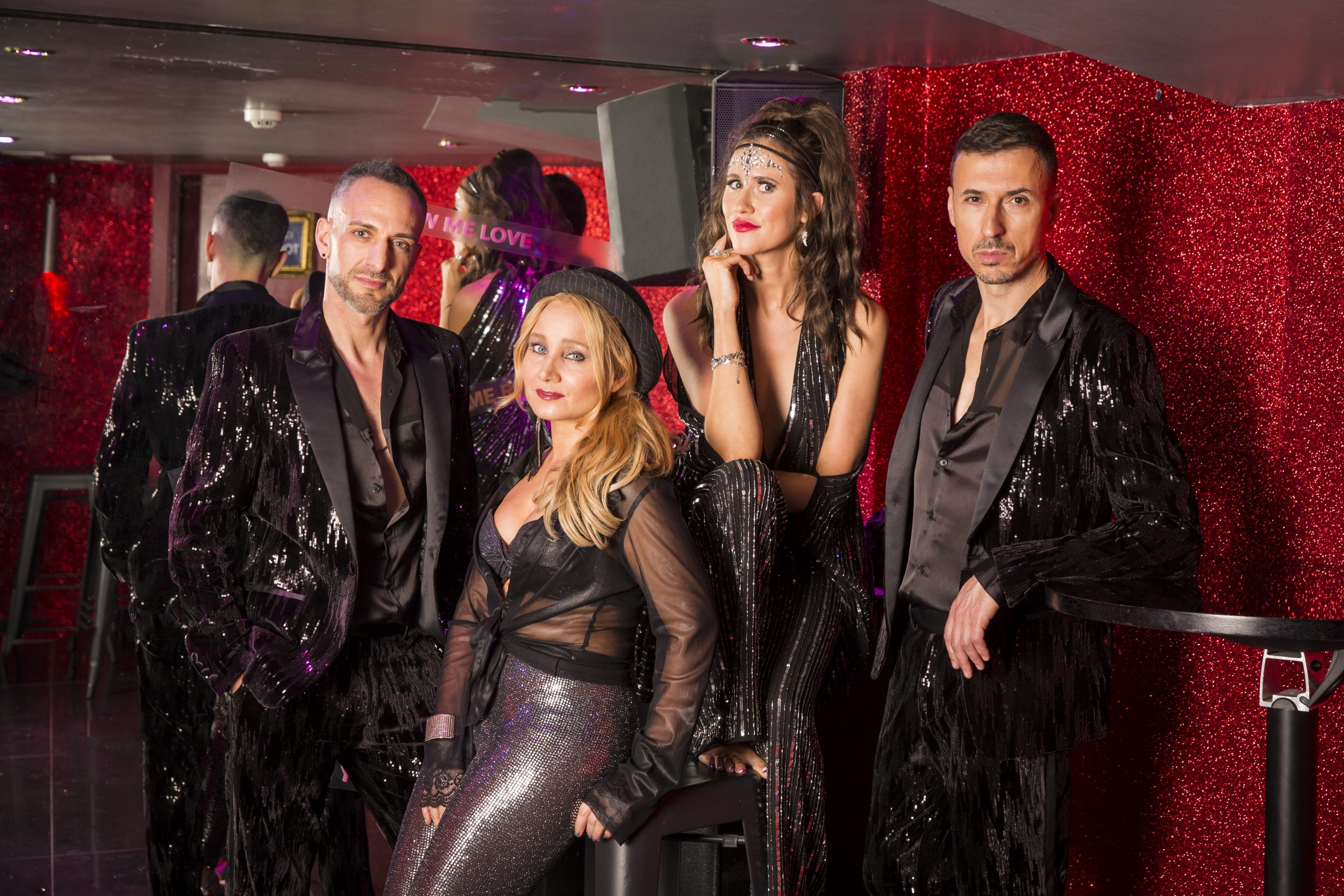 Four piece band, two male and two female in dark sequin show costumes