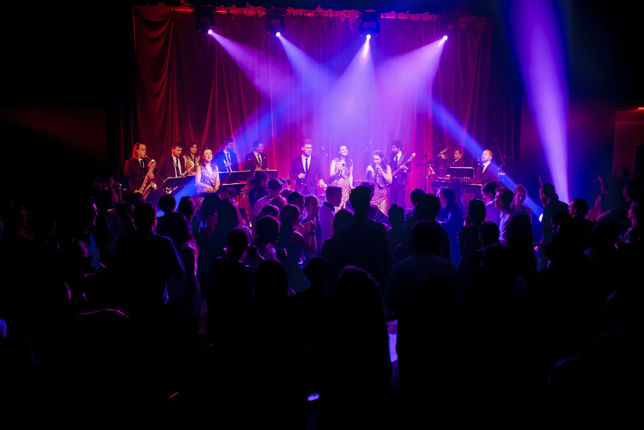 swing band on stage with pink lighting and huge crowd of guests