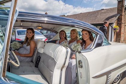 four bridesmaids in a cream vintage wedding car