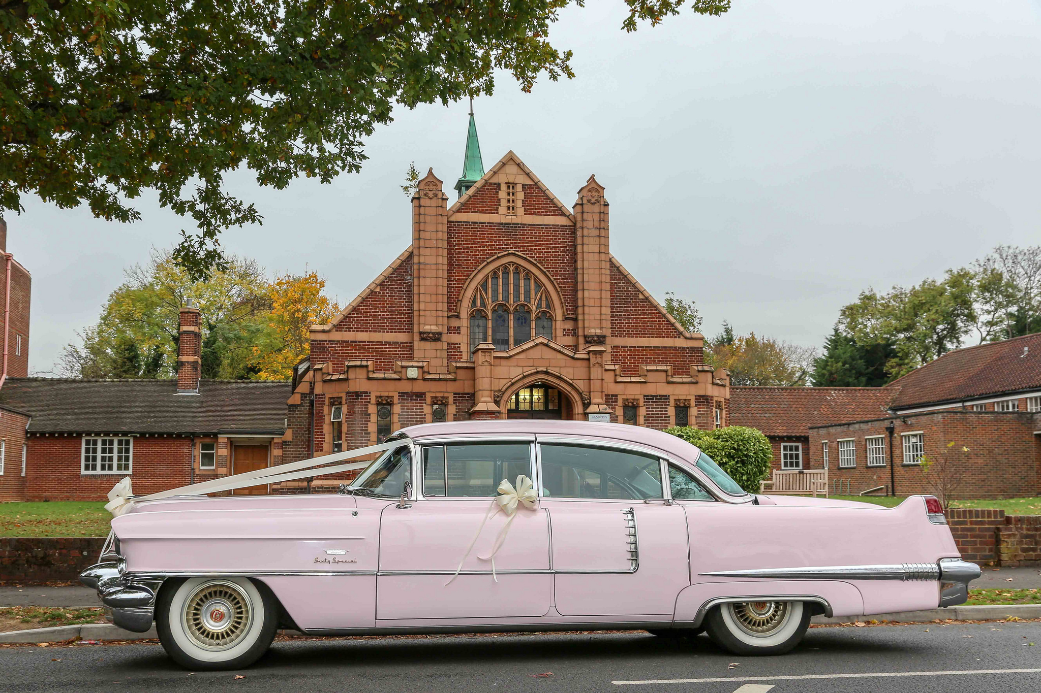 pink vintage cadillac car with white ribbons parked outside a church