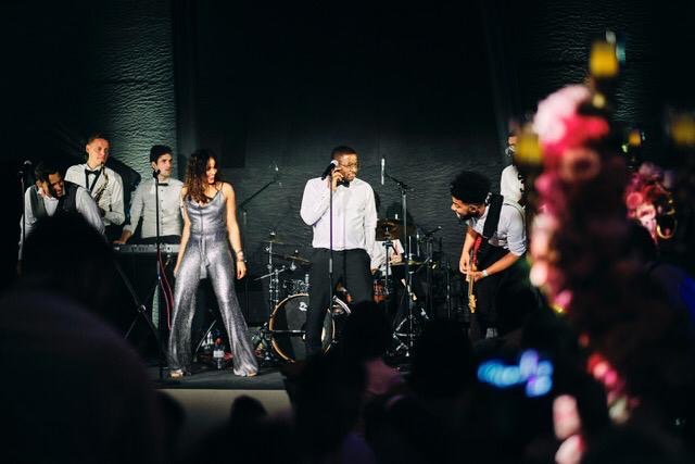 male singer plus female backing on stage with band