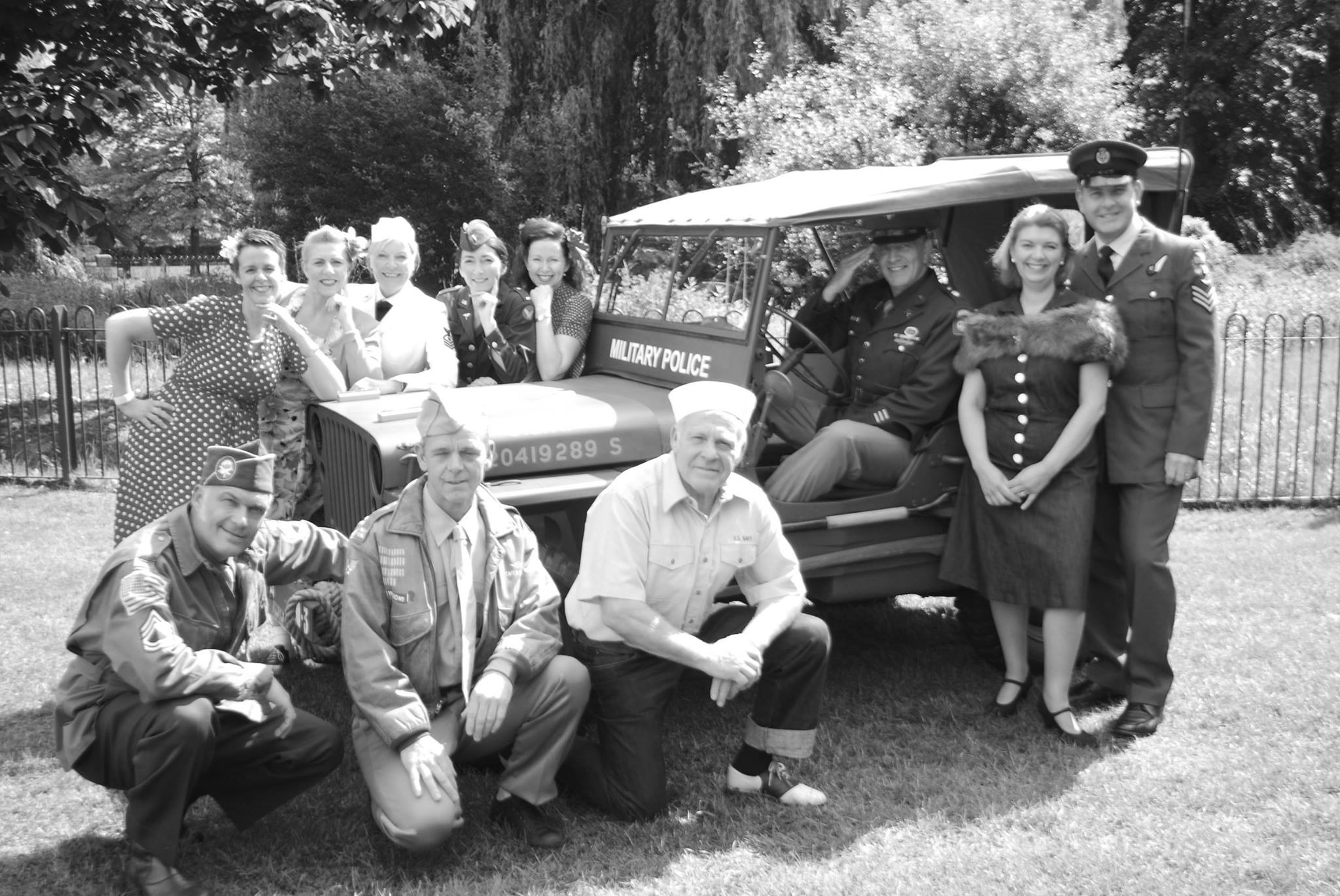 black and white photo of vintage dance group around an old car