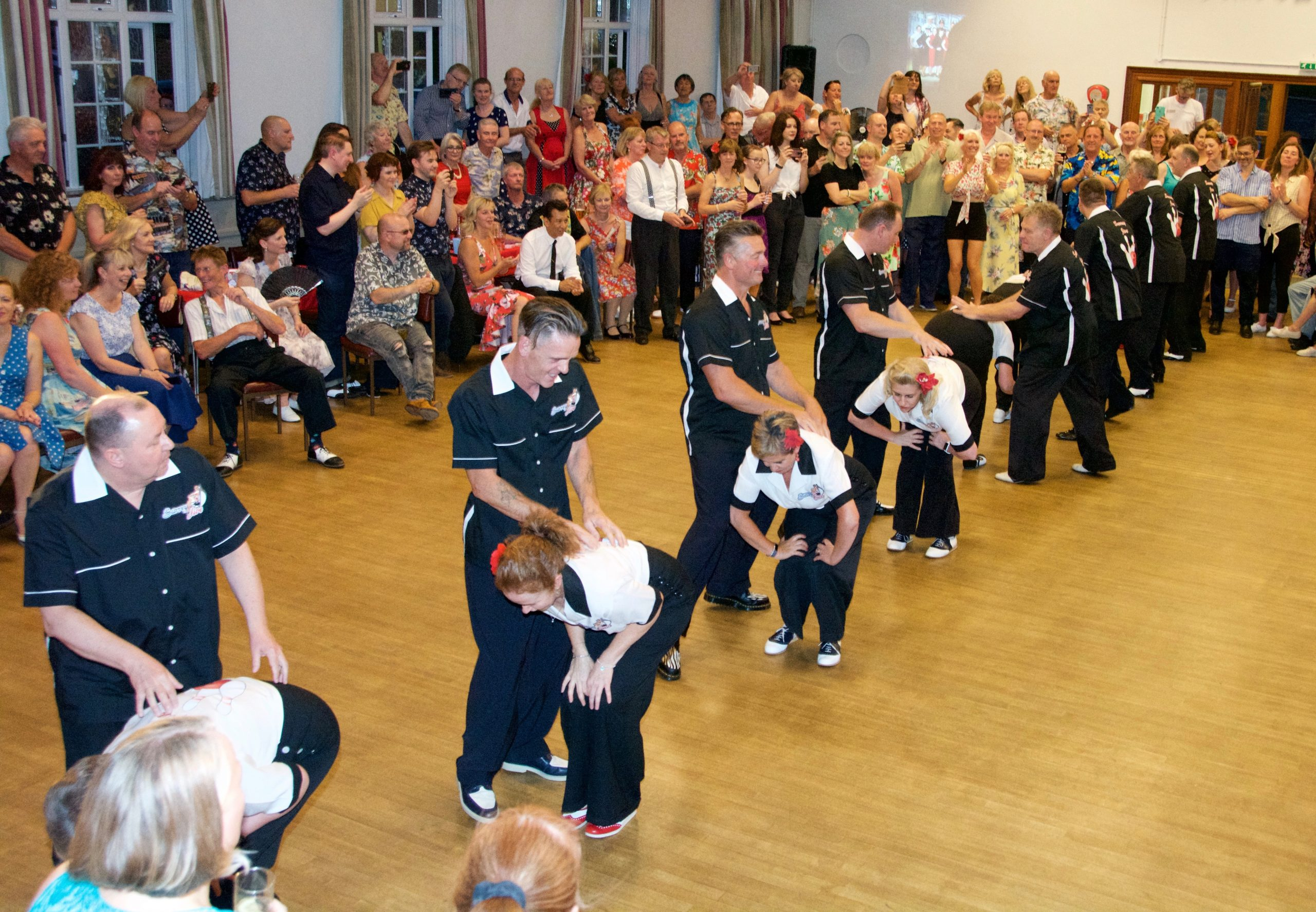 jive dancers in formation demonstrating at an event with crowd watching