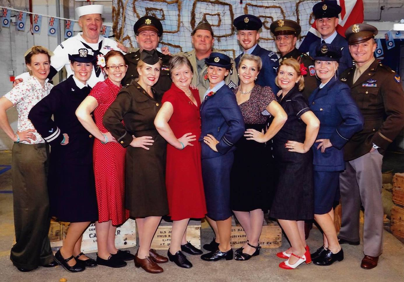 Group of 1940s and 1950s male and female dancers in wartime outfits and uniforms