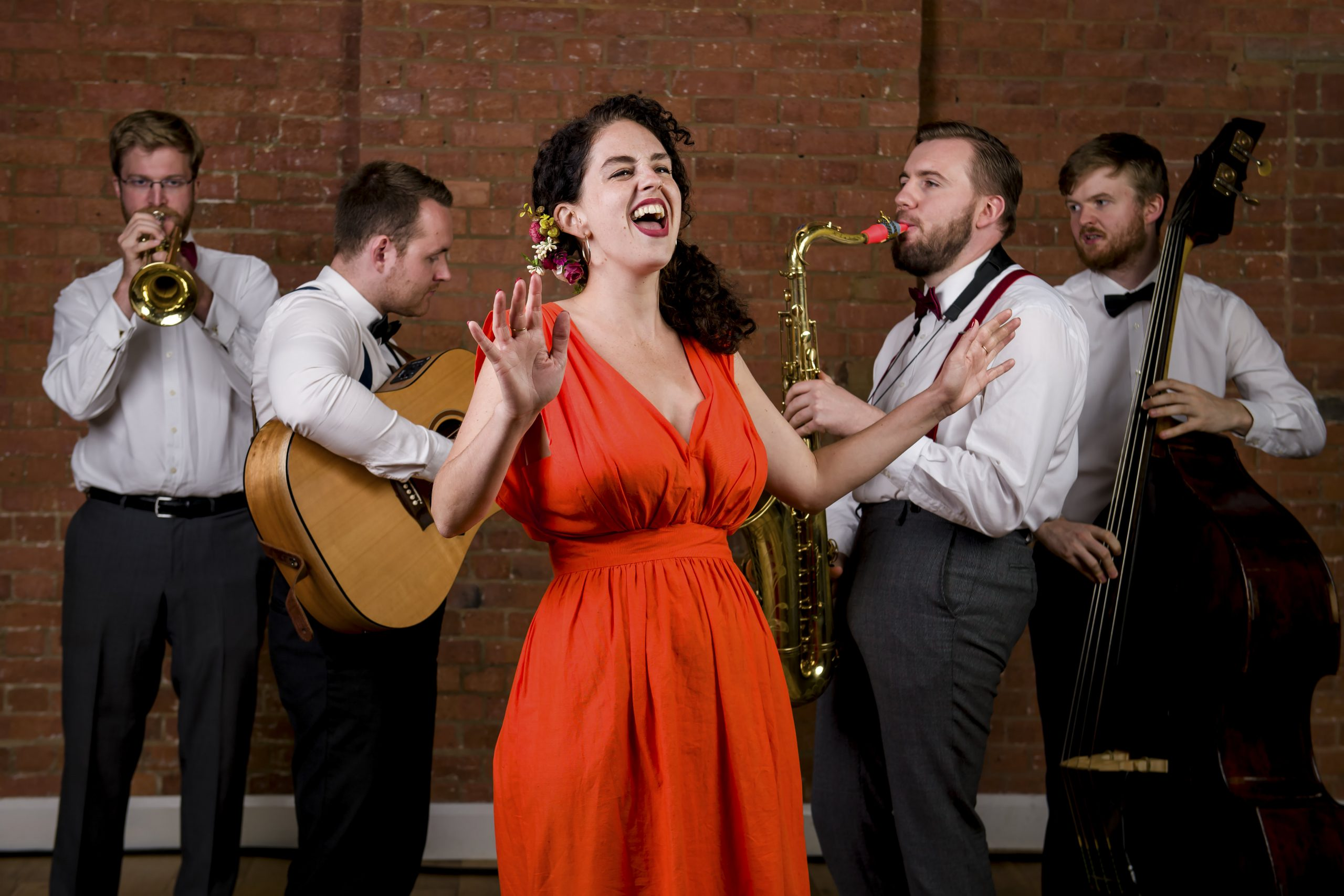 Roaming jazz band photo of guitarist, double bass player, female singer in red dress, trumpeter and saxophonist