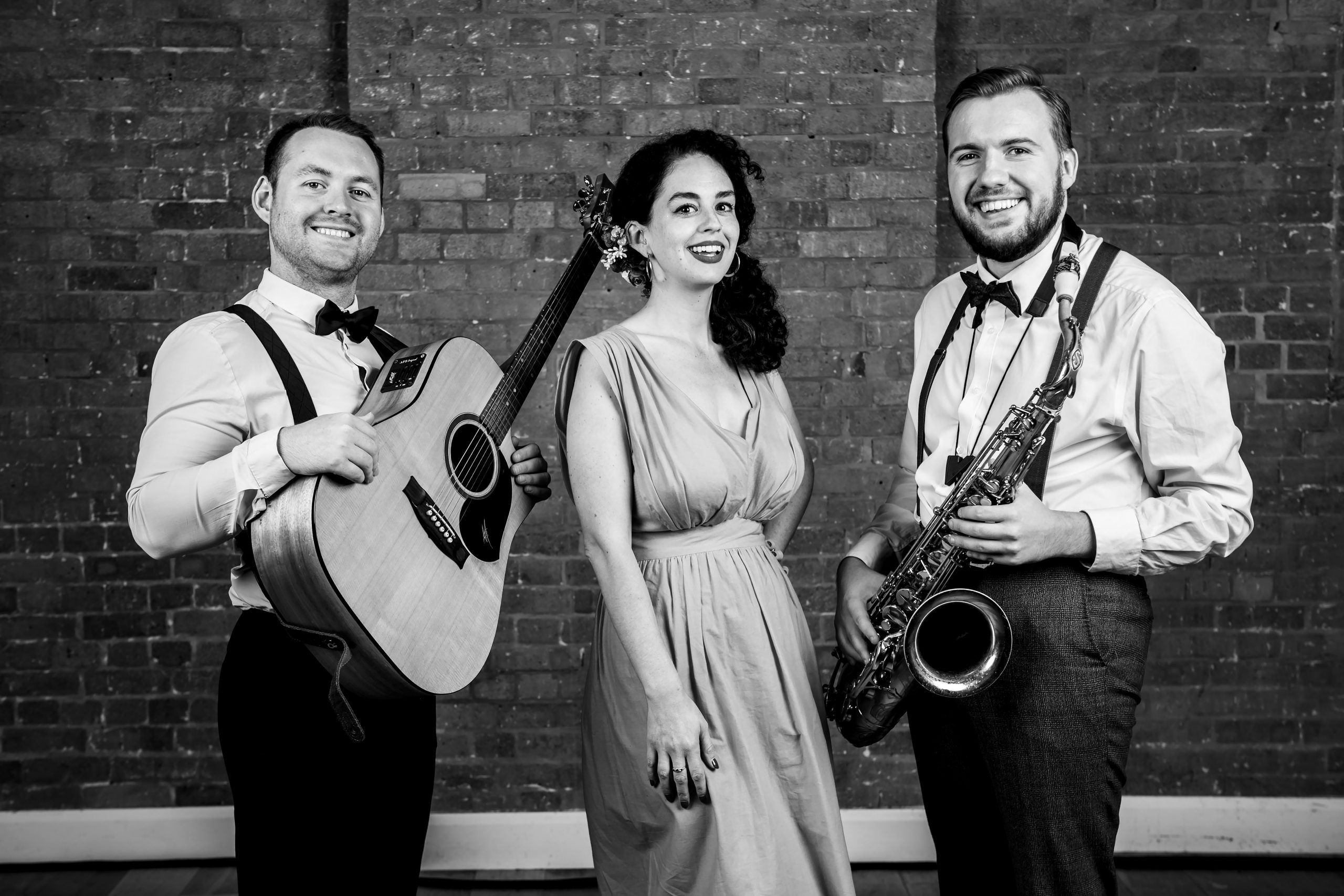 Roaming jazz band black and white photo of guitarist, female singer and saxophonist