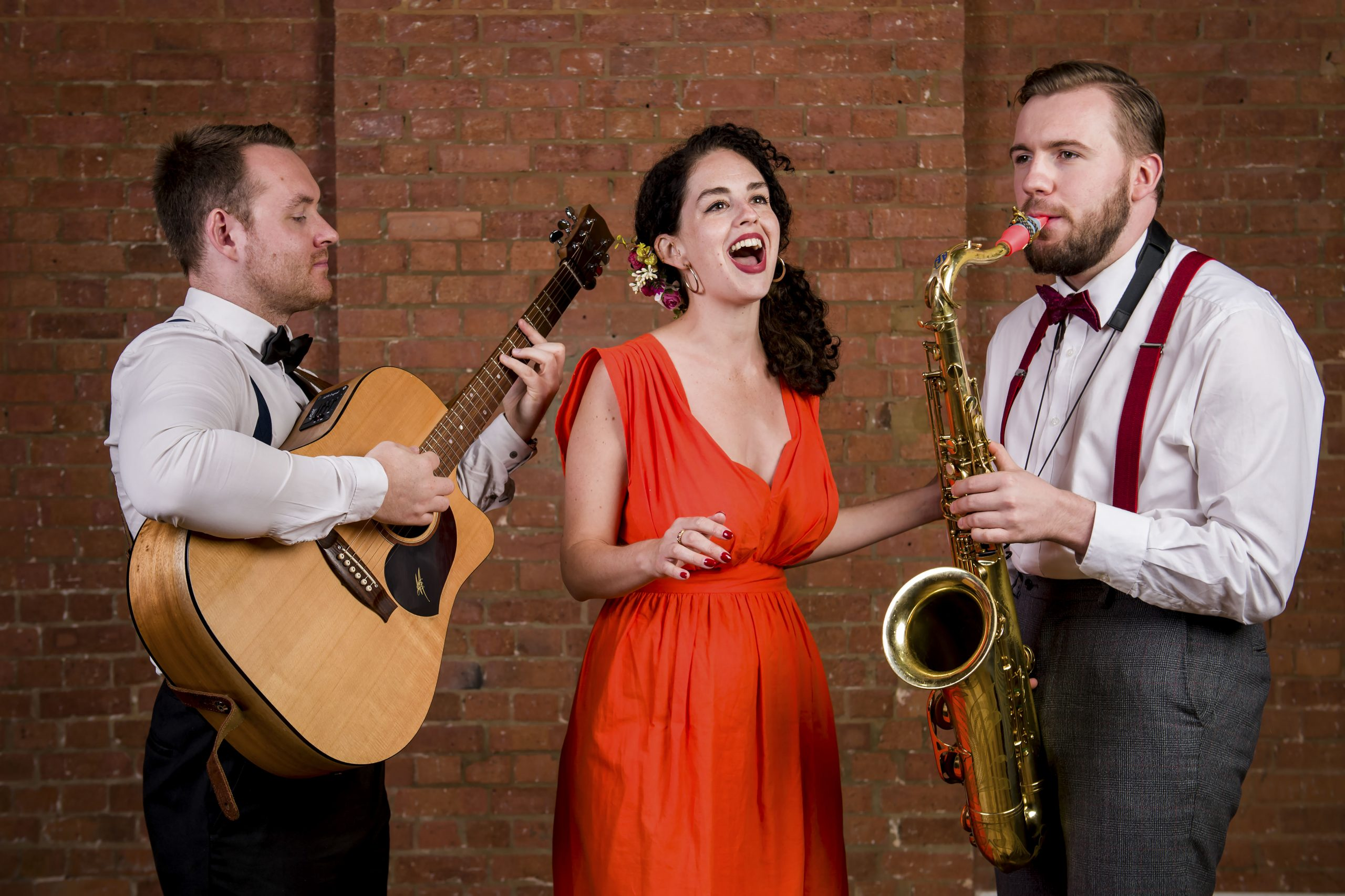 Roaming jazz band photo of guitarist, female singer in red dress and saxophonist