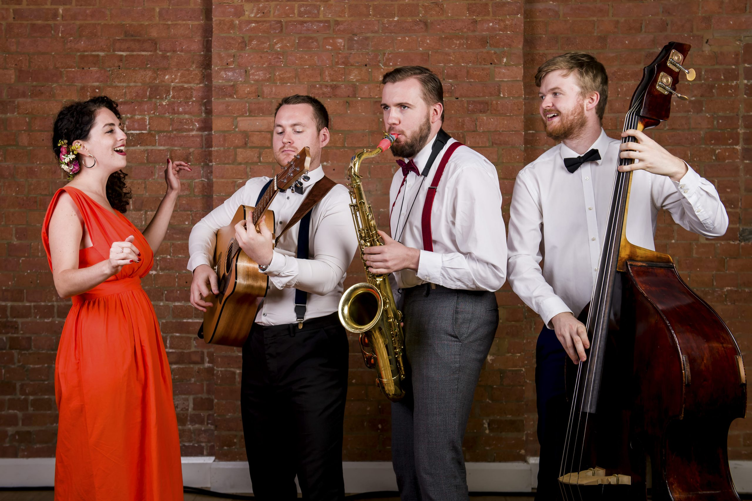 Roaming jazz band photo of guitarist, double bass player, female singer in red dress and saxophonist