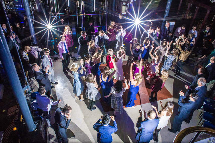 Aerial shot of wedding party dancing on the floor with ceilidh band
